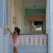 Junge Frau am öffentlichen Telefon in pastellfarbenen Häuserfluchten