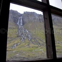 Blick aus der alten Fischfabrik in Djúpavík auf den Wasserfall