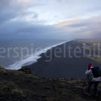 schwarze Lava-Küste beim Vogelfelsen Dyrhólaey mit Fotografin im Vordergrund, Island