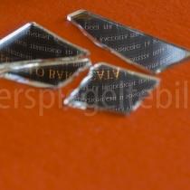 Spiegelung eines Schriftzugs in einem zerbrochenen Spiegel