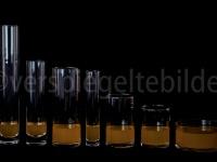 Gläser mit orangem Wasser gefüllt, alle gleich hoch