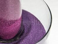 ineinandergestelle Gläser mit violettem Sand