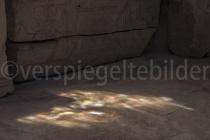 Sonne scheint durch eine bunte Glasplatte und wirft Spiegelngen auf den Steinboden