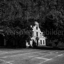 Gemeindehaus in Lioux vor einer mächtigen Felswand, schwarz-weiss