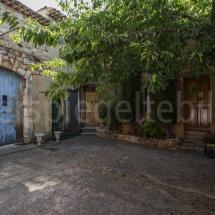Innenhof in der Altstadt von Roussillon mit Bäumen und einem blauen Tor