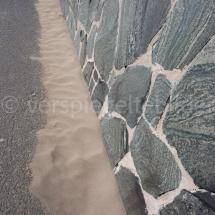 Sand entlang einer Mauer in Maspalomas