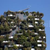 Bosco Verticale Hochhäuser mit Bepflanzung, oberster Teil mit Bewässerungsmaschine vor blauem Hintergrund
