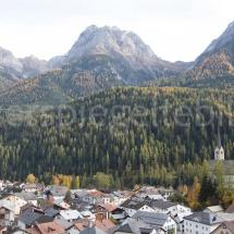 Bergpanorama mit Lärchenwältern und einem Ausschnitt aus dem Dorf